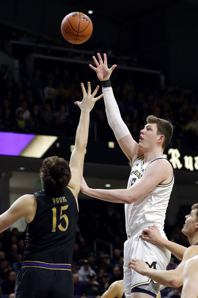 Michigan center Jon Teske, right, shoots over Northwestern center Ryan Young during the first half of an NCAA college basketball game in Evanston, Ill., Wednesday, Feb. 12, 2020. (AP Photo/Nam Y. Huh)