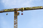 In this photo provided by Greenpeace, a banner attached to a crane reads: