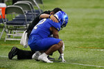 Buffalo running back Ron Cook Jr. (2) is consoled after the team lost to Ball State in the Mid-American Conference championship NCAA college football game, Friday, Dec. 18, 2020, in Detroit. (AP Photo/Carlos Osorio)