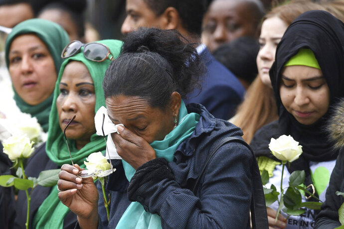 People attend a service of remembrance in west London, Thursday, June 14, 2018. A year ago, London's Grenfell Tower high-rise was destroyed by a fire that killed 72 people. It was Britain's greatest loss of life by fire since World War II. On Thursday survivors, bereaved families and people around Britain will mark the anniversary of a local tragedy that's also a national shame - one for which blame is still being traded. (Stefan Rousseau/Pool Photo via AP)