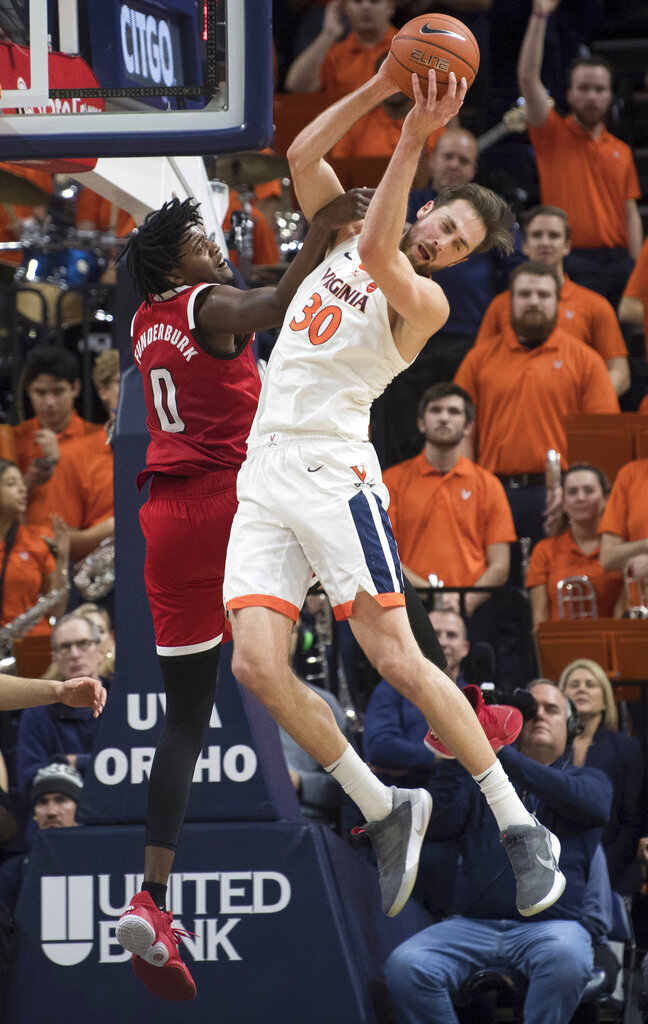 Virginia center Jay Huff (30) pulls down a rebound in front of North Carolina State forward D.J. Funderburk (0) during the first half of an NCAA college basketball game in Charlottesville, Va., Monday, Jan. 20, 2020. (AP Photo/Lee Luther Jr.)