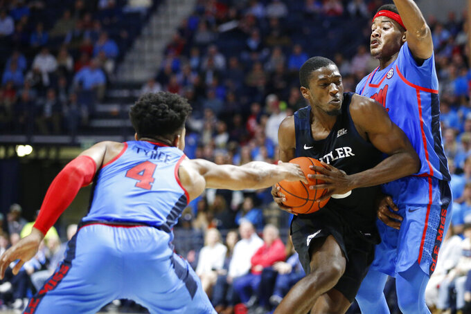 Butler guard Kamar Baldwin (3) drives toward the basket while being defended by Mississippi guards Breein Tyree (4) and Devontae Shuler during the second half of an NCAA college basketball game in Oxford, Miss., Tuesday, Dec. 3, 2019. Butler won 67-58. (AP Photo/Rogelio V. Solis)