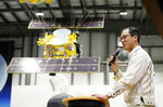 Associate Prof. Yuichi Tsuda of the Japan Aerospace Exploration Agency (JAXA) speaks about the touchdown by the Hayabusa2 near a model of the Japanese spacecraft, rear, during a press conference in Sagamihara, near Tokyo, Friday, Feb. 22, 2019. Hayabusa2 touched down on the distant asteroid Ryugu Friday on a mission to collect material that could provide clues to the origin of the solar system and life on Earth. (Kyodo News via AP)