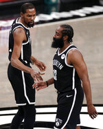 Brooklyn Nets guard James Harden (13) walks off the court past Kevin Durant early in the first quarter of Game 1 of the team's NBA basketball second-round playoff series against the Milwaukee Bucks on Saturday, June 5, 2021, in New York. (AP Photo/Adam Hunger)