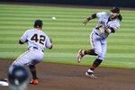 San Francisco Giants shortstop Brandon Crawford, right, flips the ball to Donovan Solano, left, for an out against the Arizona Diamondbacks in the first inning during a baseball game, Sunday, Aug 30, 2020, in Phoenix. (AP Photo/Rick Scuteri)