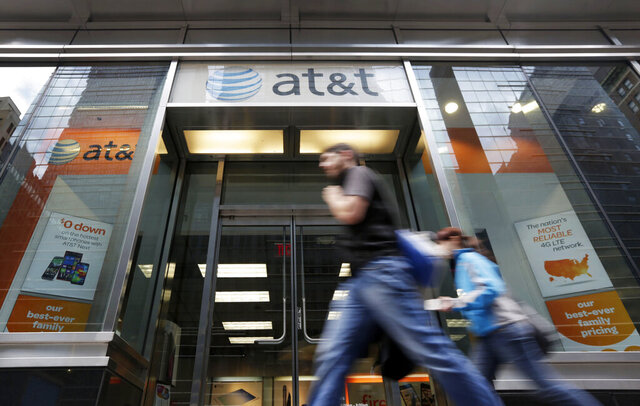 FILE - In this Oct. 21, 2014, file photo, people pass an AT&T store along New York's Madison Avenue. The nation's largest cellphone providers will pay a combined $116 million under a settlement approved Thursday, Sept. 24, 2020, in a California lawsuit alleging that they overcharged government customers for wireless services over more than a decade. Verizon will pay $68 million and AT&T Mobility $48 million to settle claims that they violated cost-saving agreements with nearly 300 state and local governments. (AP Photo/Richard Drew, File)