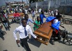 Family and friends transport the coffins that contain the remains of protesters recently killed, in Port-au-Prince, Haiti, Tuesday, Nov. 19, 2019. Hundreds of people attended the funerals for five people killed during anti-government protests, three of whom were allegedly shot by police while participating in the protests. (AP Photo/Dieu Nalio Chery)