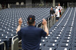 An usher at Nationals Park gestures to fans arriving and telling them to go back up after it was announced that both of today's interleague baseball games against the New York Yankees have been postponed due to inclement weather, Wednesday, May 16, 2018, in Washington. Both games have been rescheduled for June 18, 2018. (AP Photo/Pablo Martinez Monsivais)