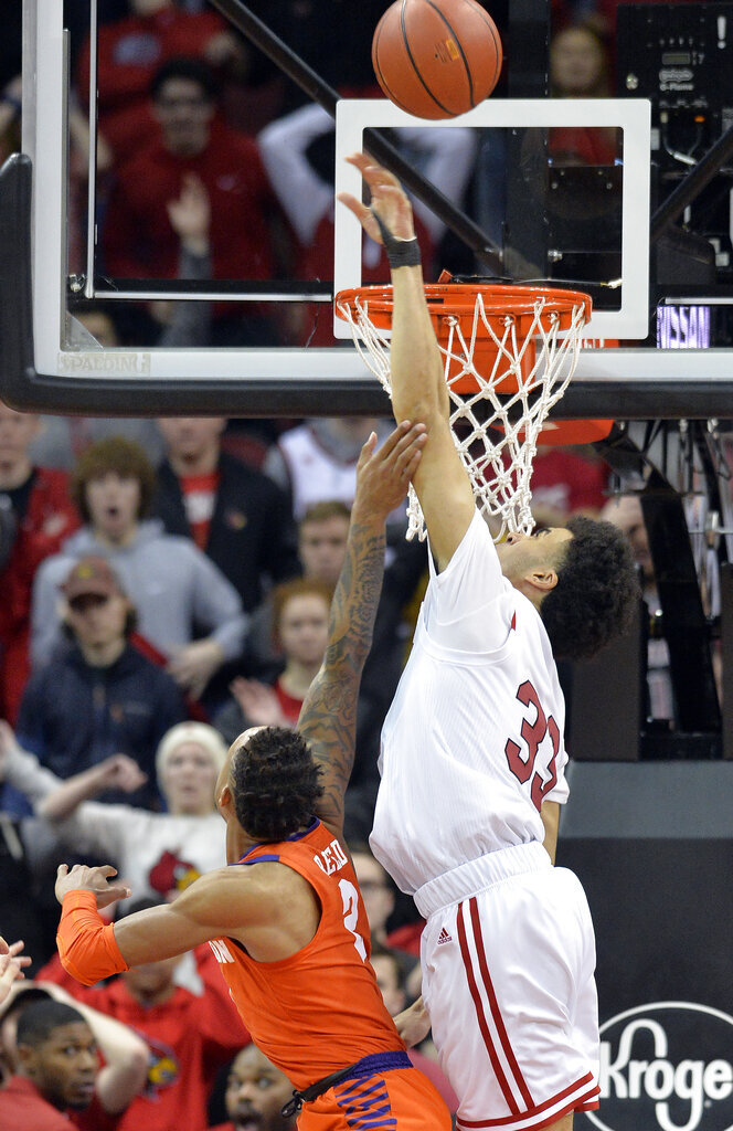 Louisville forward Jordan Nwora (33) bocks the potential game winning shot from Clemson guard Marcquise Reed (2) during the second half of an NCAA college basketball game in Louisville, Ky., Saturday, Feb. 16, 2019. Louisville won 56-55. (AP Photo/Timothy D. Easley)