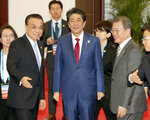 Chinese Premier Li Keqiang, left, Japan's Prime Minister Shinzo Abe, center, and South Korean President Moon Jae-in, right, walk to a photo session at the trilateral business meeting between China, South Korea and Japan in Chengdu, southwest China's Sichuan province Tuesday, Dec. 24, 2019. (Kyodo News via AP)