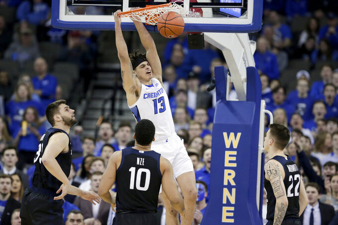 Creighton's Christian Bishop (13) dunks over Butler's Bryce Golden (33), Bryce Nze (10) and Sean McDermott (22) during the first half of an NCAA college basketball game in Omaha, Neb., Sunday, Feb. 23, 2020. (AP Photo/Nati Harnik)