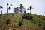 A blue-striped structure sits on a lookout point on Little St. James Island, in the U. S. Virgin Islands, a property owned by Jeffrey Epstein, Wednesday, Aug. 14, 2019. Epstein bought Little St. James Island more than two decades ago and built a stone mansion with cream-colored walls on one end of it. Surrounding it are several other structures including the maids' quarters and the huge, square-shaped, blue-striped building on the other end of the island that workers told each other was a music room fitted with a grand piano and acoustic walls. (AP Photo/Gabriel Lopez Albarran)