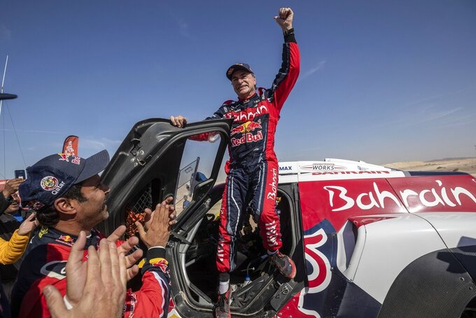 Driver Carlos Sainz, of Spain, celebrates at the end of stage twelve of the Dakar Rally between Haradth and Qiddiya, Saudi Arabia, Friday, Jan. 17, 2020. Sainz, 57, won a third Dakar Rally (AP Photo/Bernat Armangue)