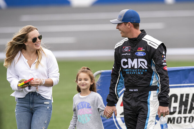 NASCAR Xfinity Series driver Ryan Sieg (39) walks with his family after driver introductions prior to the NASCAR Xfinity auto racing race at the Charlotte Motor Speedway Sunday, Oct. 10, 2021, in Concord, N.C. (AP Photo/Matt Kelley)