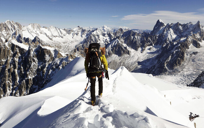 FILE - In this file photo taken on Oct. 12, 2011, an alpinist heads down a ridge on the Aiguille du Midi (3,842 meters; 12 605 feet), towards the Vallee Blanche on the Mont Blanc massif, in the Alps, near Chamonix. French President Emmanuel Macron declared the battle against climate change and environmental destruction to be