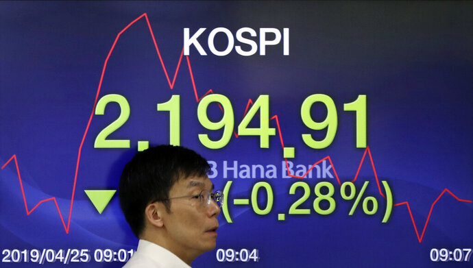 A currency trader walks by the screen showing the Korea Composite Stock Price Index (KOSPI) at the foreign exchange dealing room in Seoul, South Korea, Thursday, April 25, 2019. Asian shares were mixed Thursday after U.S. stocks closed lower, giving back some of its gains a day after the S&P 500 and Nasdaq hit record highs. (AP Photo/Lee Jin-man)