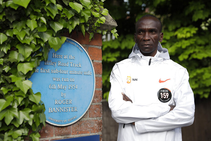 FILE - In this Tuesday, April 30, 2019 file photo, marathon world record holder Kenya's Eliud Kipchoge poses for photographers at the Iffley Road Track, in Oxford, England. Kipchoge's attempt to run a sub two-hour marathon has been set for Saturday, Oct. 12 in Prater park, a landmark part of the Vienna City Marathon. Event organizers decided Wednesday to stick to the first planned race date, although they initially used a nine-day window to allow rescheduling for any unfavorable weather conditions. (AP Photo/Matt Dunham, file)