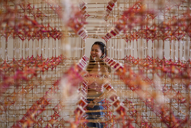 A woman looks through an art installation of Rattana Sudjarit at the Bangkok Art and Cultural Center in Bangkok, Thailand, Tuesday, June 23, 2020. Daily life in the capital is resuming to normal as the Thai government continues to ease restrictions related to running business and activities that were imposed weeks ago to combat the spread of COVID-19. (AP Photo/ Gemunu Amarasinghe)