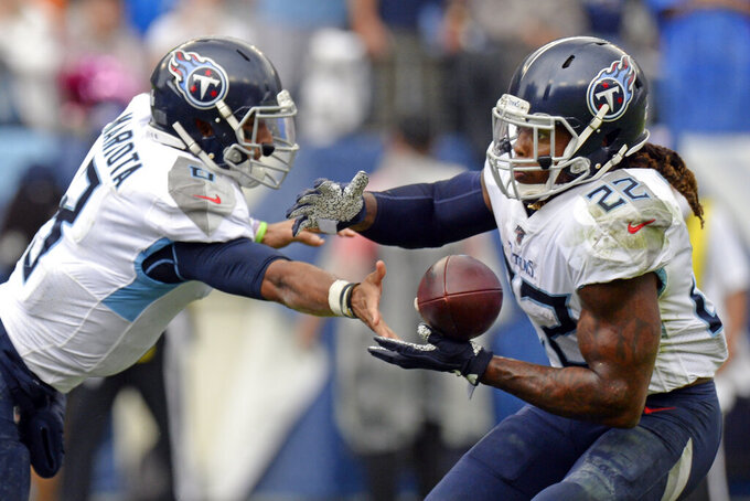 Tennessee Titans running back Derrick Henry (22) takes a handoff from quarterback Marcus Mariota (8) as Henry scores a touchdown on a 1-yard run against the Buffalo Bills in the second half of an NFL football game Sunday, Oct. 6, 2019, in Nashville, Tenn. (AP Photo/Mark Zaleski)