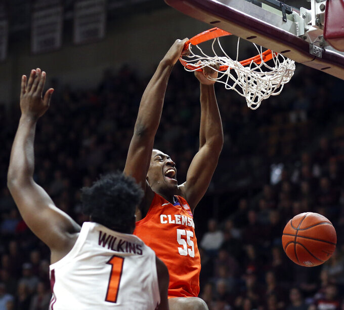 Clemson's Trey Jemison (55) scores past Virginia Tech's Isaiah Wilkins (1) during the first half of an NCAA college basketball game Wednesday, March 4, 2020, in Blacksburg, Va. (Matt Gentry/The Roanoke Times via AP)