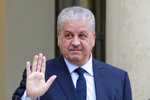 FILE - In this Dec.4, 2014 file photo, former Algerian Prime Minister Abdelmalek Sellal waves to reporters as he leaves the Elysee Palace following his meeting with French President Francois Hollande in Paris. Abdelmalek Sellal was sentenced to 12 years in prison and $8,000 in fines. (AP Photo/Remy de la Mauviniere, File)