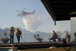 Firefighters watch as a helicopter drops water in a wildfire in the Pacific Palisades area of Los Angeles, Monday, Oct. 21, 2019. (AP Photo/Christian Monterrosa)