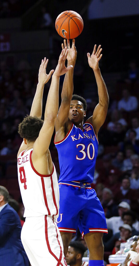 Kansas guard Ochai Agbaji (30) shoots over Oklahoma center Jamuni McNeace (4) in the first half of an NCAA college basketball game in Norman, Okla., Tuesday, March 5, 2019. (AP Photo/Nate Billings)