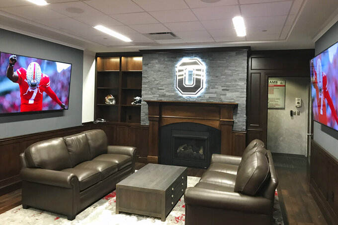 This Saturday, Aug. 23, 2019, photo provided by Ohio State Athletics shows the NCAA college football head coach's office at the Woody Hayes Center on the Ohio State campus in Columbus, Ohio. The head coach's office is right off the locker room. A player could step out of one and right into the other. To encourage the Buckeyes to do just that, Ryan Day made a few changes to the space since taking over for Urban Meyer. (Jerry Emig/Ohio State Athletics via AP)