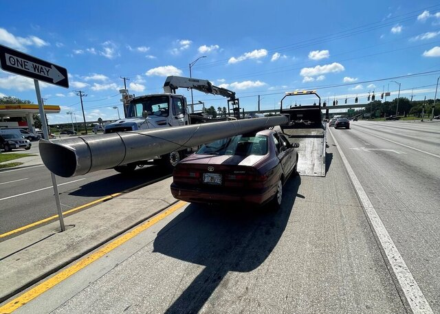 In this photo provided by the Florida Highway Patrol a downed power pole is strapped to the roof of a car, Monday, Nov. 16, 2020, on Interstate 4, in Hillsborough County, Fla. A state trooper pulled over a maroon Toyota Camry with a metal light pole, longer than the car itself, strapped to the roof on a Tampa road Monday morning, according to a Florida Highway Patrol report. The Camry's driver, Douglas Allen Hatley, told troopers that he had found the pole on the ground by the side of the highway and had planned to sell the metal for scrap, according to the report.  Hatley charged with grand theft was being held on $2,000 bond. (Florida Highway Patrol via AP)