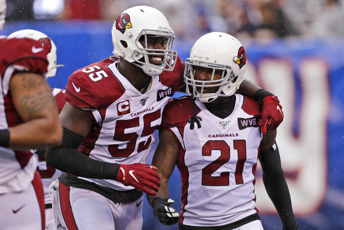 FILE - In this Sunday, Oct. 20, 2019 file photo, Arizona Cardinals' Patrick Peterson, right, celebrates forcing a fumble with Chandler Jones (55) during the second half of an NFL football game against the New York Giants in East Rutherford, N.J. The Cardinals locker room was a jovial place on Tuesday, Nov. 19, 2019, with players rushing through their post-practice routine so they could embark on a five-day break away from football. (AP Photo/Adam Hunger, File)