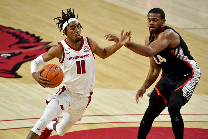 Arkansas guard Jalen Tate (11) tries to drive past Georgia defender P.J. Horne (24) during the second half of an NCAA college basketball game Saturday, Jan. 9, 2021, in Fayetteville, Ark. (AP Photo/Michael Woods)