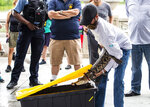 Florida alligator expert Frank Robb removes an alligator from a plastic holding container during a news conference, Tuesday, July 16, 2019, in Chicago. Robb captured the elusive alligator in a public lagoon at Humboldt Park early Tuesday. (Ashlee Rezin/Chicago Sun-Times via AP)