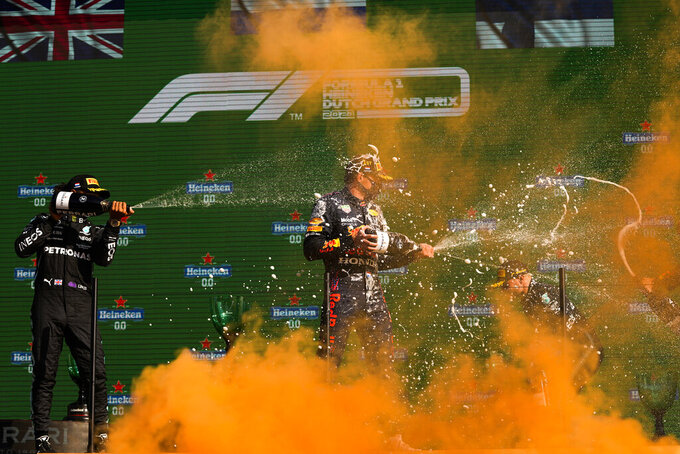 Red Bull driver Max Verstappen, center, of the Netherlands, sprays champagne on the podium next to Mercedes driver Lewis Hamilton, left, of Britain, second position, and Mercedes driver Valtteri Bottas of Finland, third position, after winning the Formula One Dutch Grand Prix, at the Zandvoort racetrack, Netherlands, Sunday, Sept. 5, 2021. (AP Photo/Francisco Seco)