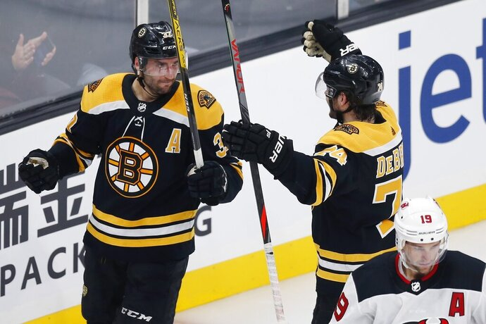 Boston Bruins' Patrice Bergeron (37) celebrates his goal with Jake DeBrusk (74) as New Jersey Devils' Travis Zajac (19) skates away during the second period of an NHL hockey game in Boston, Saturday, Oct. 12, 2019. (AP Photo/Michael Dwyer)
