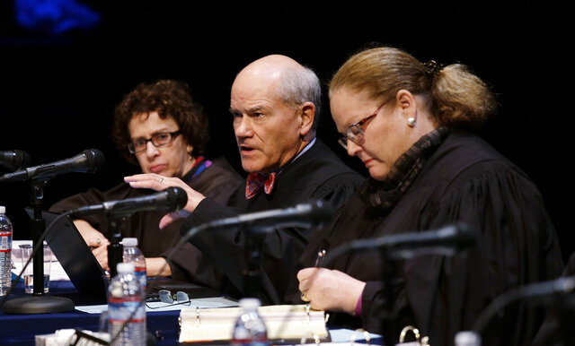 FILE - In this Nov. 15, 2016, file photo Washington Supreme Court Justice Charles K. Wiggins, second left, speaks as fellow Justices Sheryl Gordon McCloud, left, and Mary E. Fairhurst listen during arguments in Bellevue, Wash. Wiggins, 72, announced Thursday, Jan. 16, 2020, he will retire at the end of March. Wiggins was first elected to the court in 2010. (AP Photo/Elaine Thompson, File)