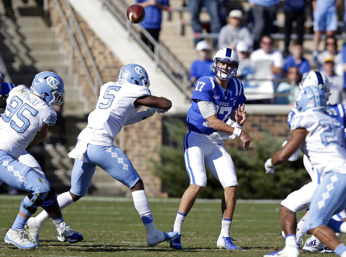 Duke quarterback Daniel Jones (17) passes as North Carolina's Tyler Powell (95) and Patrice Rene (5) pressure during the first half of an NCAA college football game in Durham, N.C., Saturday, Nov. 10, 2018. (AP Photo/Gerry Broome)