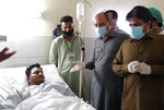 In this photo released by the Sindh Press Information Department, Pakistani provincial minister Saeed Ghani, second from right, meets Mohammad Zubair who survived a plane crash, at a hospital in Karachi, Pakistan, Friday, May 22, 2020. An aviation official says a passenger plane belonging to state-run Pakistan International Airlines carrying passengers and crew has crashed near the southern port city of Karachi. ((Sind Press Information Department, via AP)