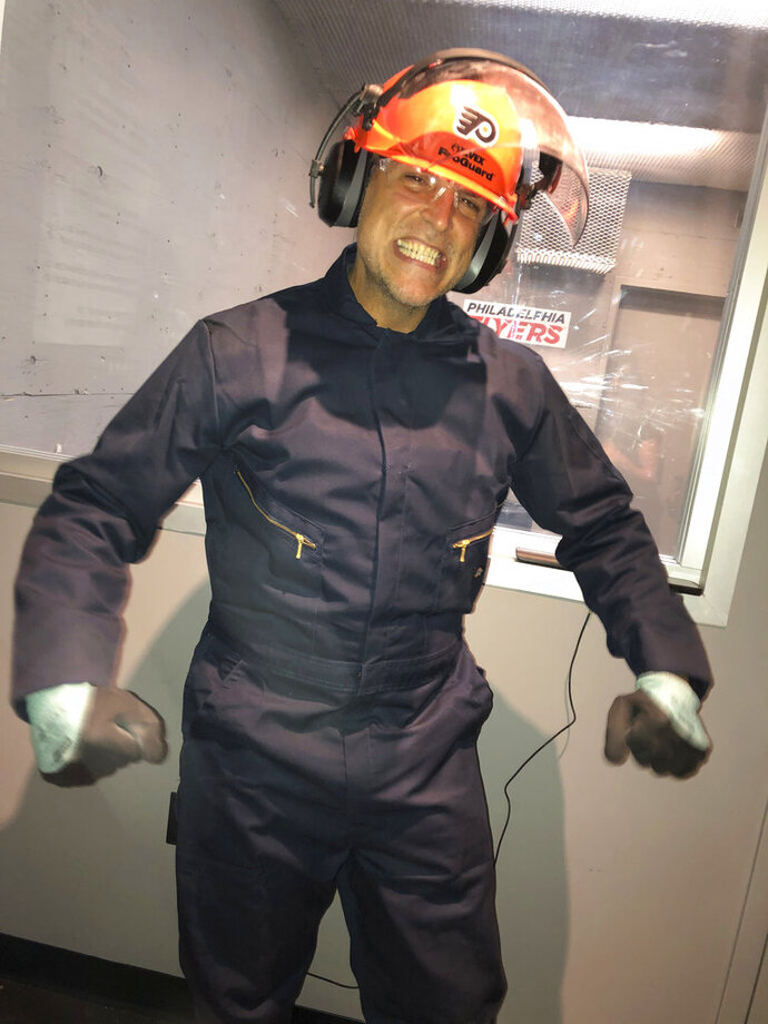 Peter Caccioppoli, a Philadelphia Flyers fan from New York, wears a jumpsuit and safety helmet in the
