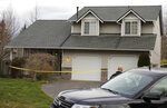 Crime scene tape surrounds a home, Tuesday, March 13, 2018, in Spanaway, Wash., where authorities say a member of the U.S. Air Force, who was stationed at Joint Base Lewis-McChord, fatally shot his two young children and their mother before killing himself overnight. (AP Photo/Ted S. Warren)