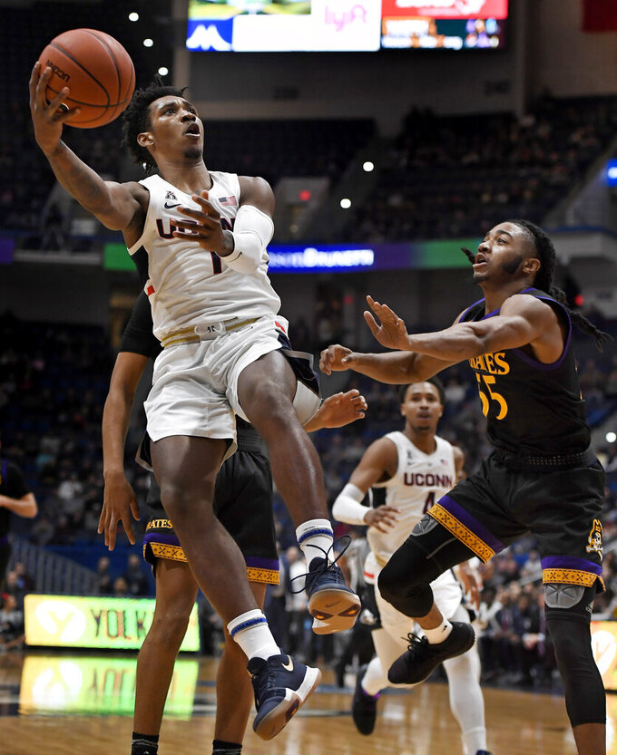 Connecticut's Christian Vital (1) shoots as East Carolina's Shawn Williams (55) defends during the first half of an NCAA college basketball game, Sunday, Feb. 3, 2019, in Hartford, Conn. (AP Photo/Jessica Hill)