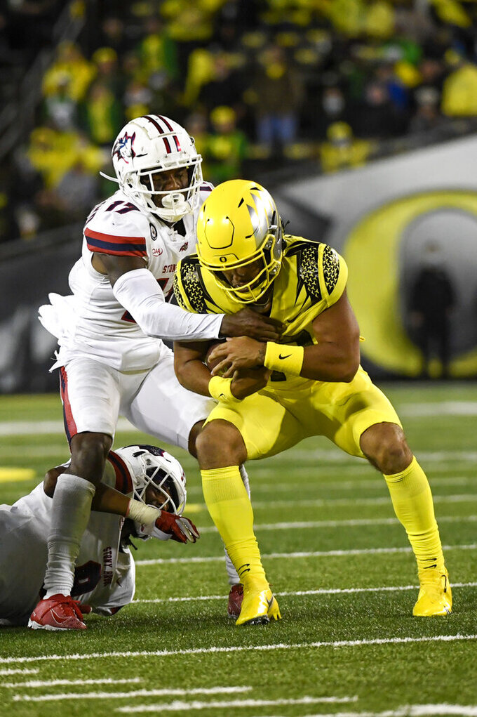 Stony Brook defensive back Carthell Flowers, left, sacks Oregon quarterback Ty Thompson, right, during the fourth quarter of an NCAA college football game Saturday, Sept. 18, 2021, in Eugene, Ore. (AP Photo/Andy Nelson)