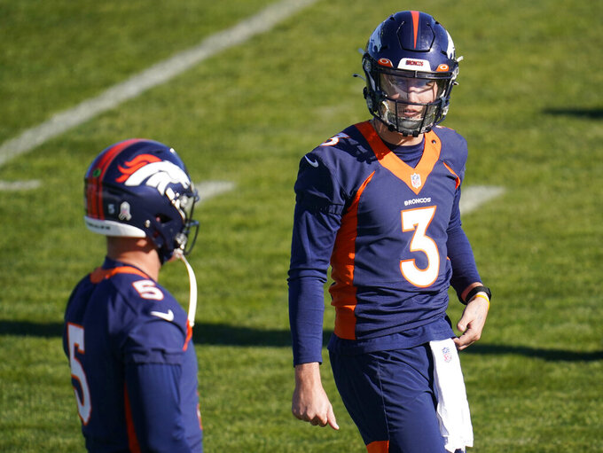 FILE - Denver Broncos quarterback Drew Lock (3) confers with quarterback Riley Neal as they take part in drills during an NFL football practice at the team's headquarters in Englewood, Colo., in this in this file Wednesday, Nov. 25, 2020, file photo. The Broncos activated three quarterbacks—starter Lock and backups Brett Rypien and Blake Bortles—on Tuesday, Dec. 1, from the COVID-19 list to insure that the team has quarterbacks on the roster for Sunday's game against division-rival Chiefs in Kansas City unlike this past Sunday's game against New Orleans when the Broncos had no signal-callers to take the gridiron. (AP Photo/David Zalubowski, File)