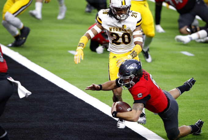 UNLV quarterback Max Gilliam (6) dives into the end zone for a touchdown ahead of Wyoming cornerback Azizi Hearn (20) during the first half of an NCAA college football game in Las Vegas on Friday, Nov. 27, 2020. (Steve Marcus/Las Vegas Sun via AP)