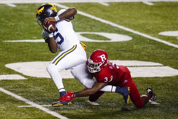 Rutgers' Olakunle Fatukasi (3) sacks Michigan quarterback Joe Milton (5) during the first half of an NCAA college football game Saturday, Nov. 21, 2020, in Piscataway, N.J. (AP Photo/Frank Franklin II)