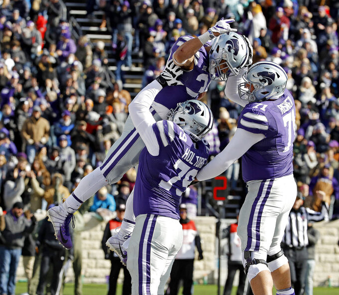 Kansas State running back Alex Barnes (34) celebrates with offensive linemen Adam Holtorf (79) and Dalton Risner (71) after scoring a touchdown during the second half of an NCAA college football game against Kansas, Saturday, Nov. 10, 2018, in Manhattan, Kan. Kansas State won 21-17. (AP Photo/Charlie Riedel)
