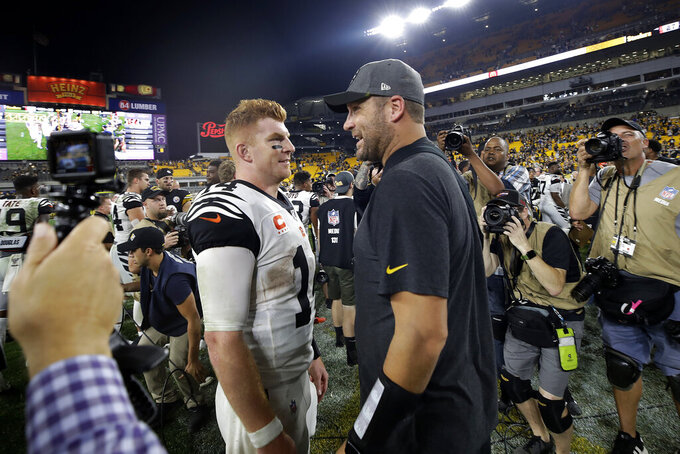Injured Pittsburgh Steelers quarterback Ben Roethlisberger, right center, talks with Cincinnati Bengals quarterback Andy Dalton (14) following an NFL football game in Pittsburgh, Monday, Sept. 30, 2019.  (AP Photo/Don Wright)