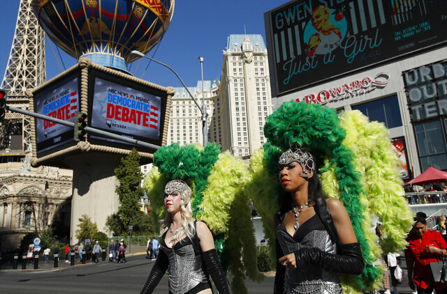 FILE - In this Feb. 19, 2020, file photo, people dressed as showgirls walk near the Paris Las Vegas hotel casino, site of a Democratic presidential debate in Las Vegas. Just past the roulette wheel and slot machines, the smoky bars and blinking lights, Nevada Democrats are preparing to weigh in on their party's presidential nomination fight. (AP Photo/John Locher, File)