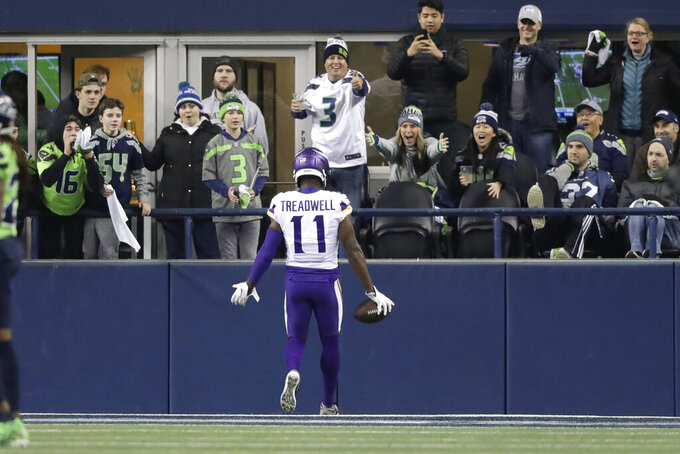 Seattle Seahawks fans react as Minnesota Vikings' Laquon Treadwell runs through the end zone after scoring during the second half of an NFL football game Monday, Dec. 2, 2019, in Seattle. (AP Photo/John Froschauer)