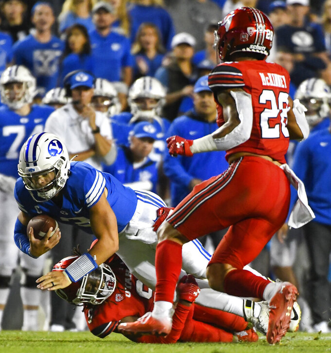 Utah safety Vonte Davis, bottom, tackles Brigham Young quarterback Jaren Hall, top, during the second half of an NCAA college football game Saturday, Sept. 11, 2021, in Provo, Utah. (AP Photo/Alex Goodlett)