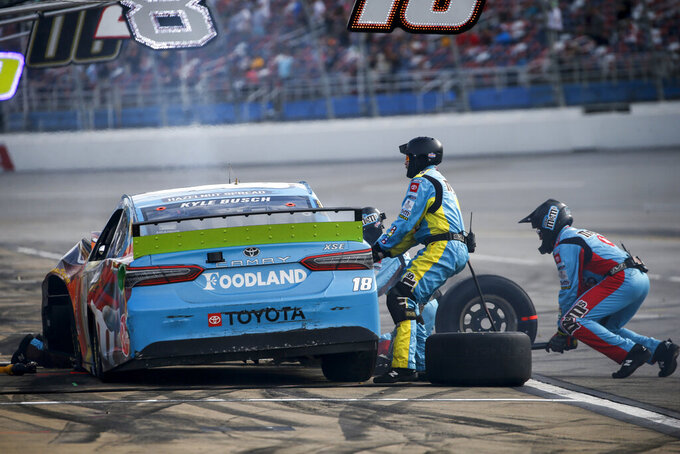 Crew members work on Kyle Busch's car after a wreck during a NASCAR Cup Series auto race at Talladega Superspeedway, Monday, Oct 14, 2019, in Talladega, Ala. (AP Photo/Butch Dill)